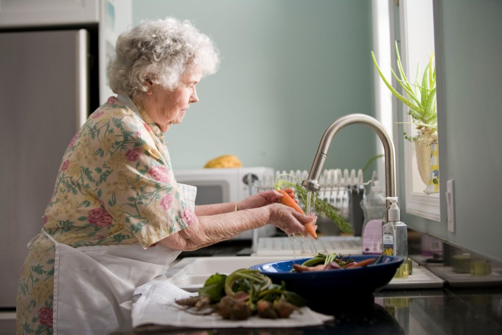 Elderly women washing carrots in kitchen sink. A bowl of other vegetables sits on the counter nearby.