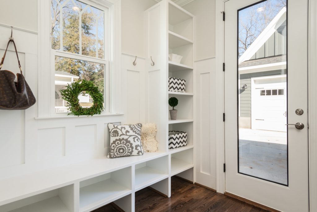 Mudroom interior with shelving and hooks for storage. Built-in bench has shelving underneath. Door to the right of image has a large window pane, showing garage in distance.
