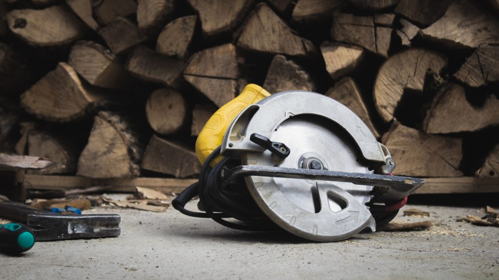 A circular saw lays on the floor in front of a pile of wood.
