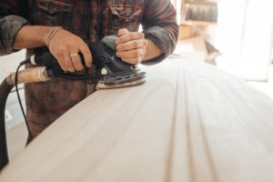 A person using an electric dander to smooth a wide plank of wood. Their clothes are covered in wood shavings.