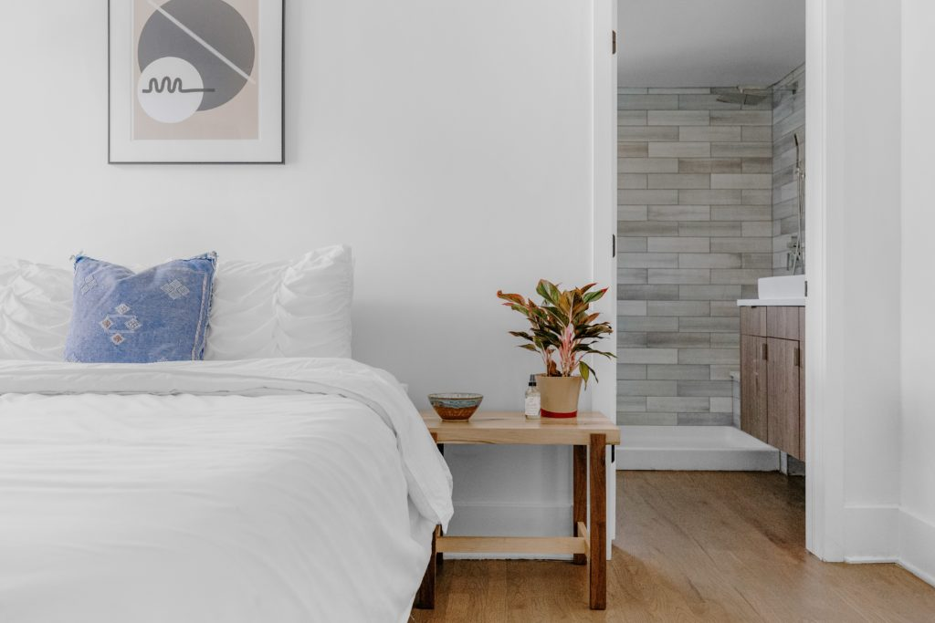 Bed with white sheets and wooden end table. En suite bathroom in distance.