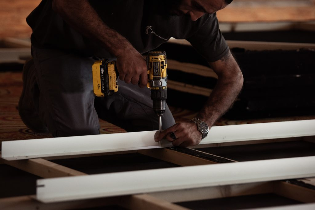 A man uses a drill to attach a thin metal beam to wooden framework.